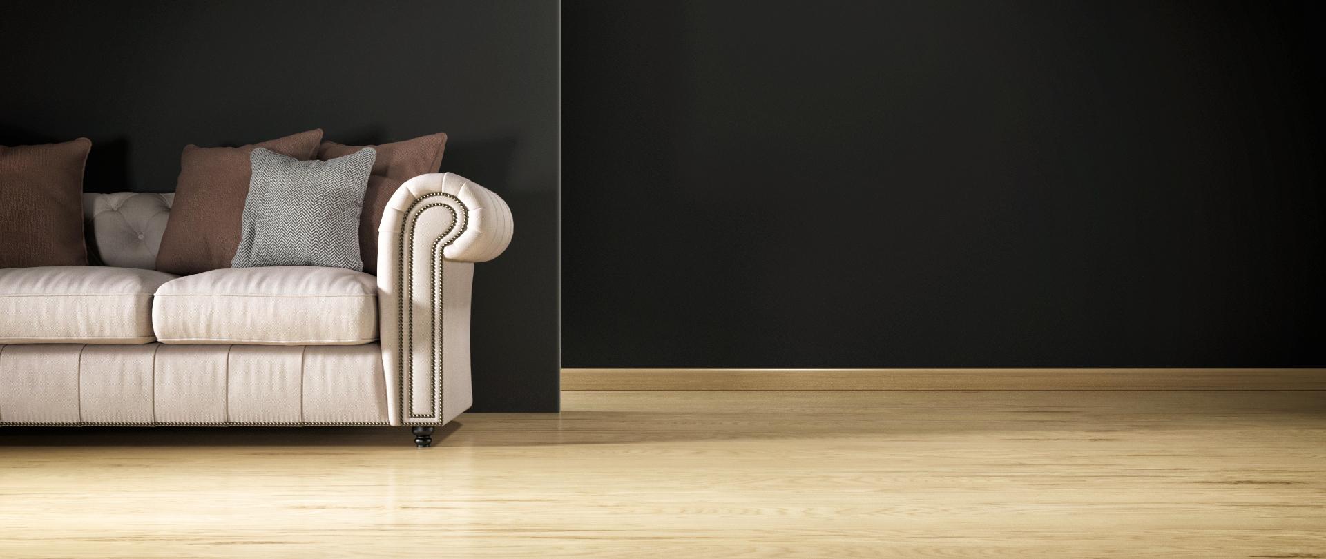 Imagen de cabecera. Aparece un sofá clásico sobre suelo de tarima de madera clara delante de tabiquería negra.