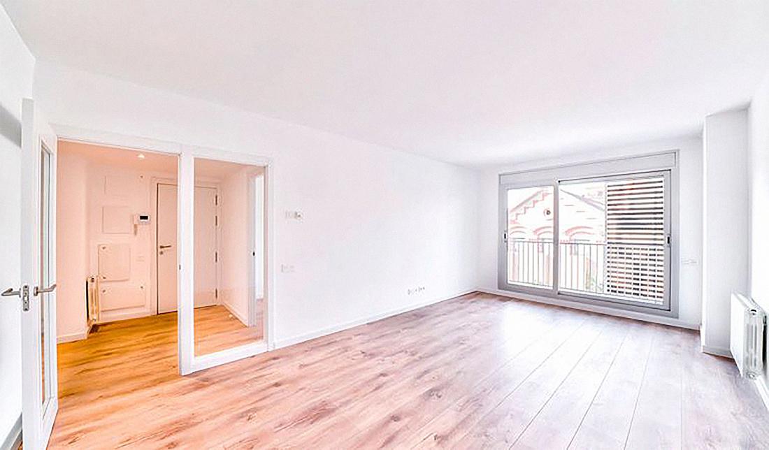 Fotografía de salón de vivienda sin amueblar. Suelo imitando madera de pino y tabiquería blanca.