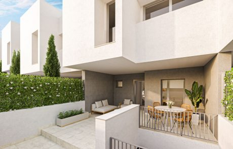 Render exterior de patio con laterales ajardinados. La vivienda tiene un monocapa gris oscuro en la planta baja y un monocapa blanco en la primera planta.