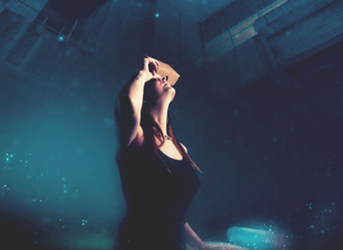 Fotografía de mujer usando un visor tipo cardboard con fondo en tonos azules.