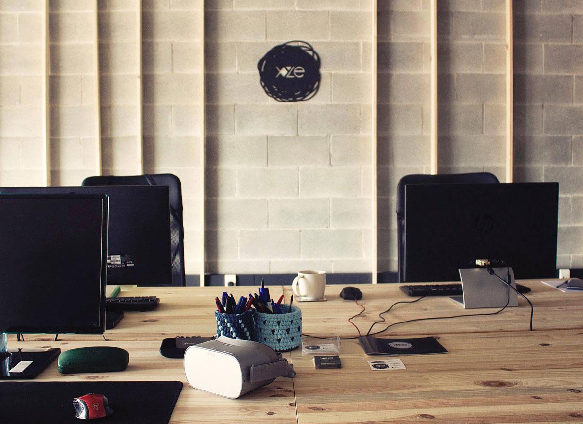 Fotografía del estudio XYZE, en la que se ven los tres puestos de trabajo y el visor Oculus Go.